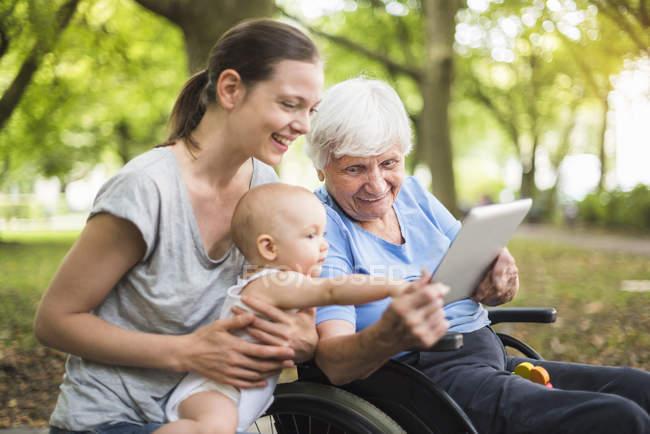 Abuela, hija y nieta divirtiéndose con la tableta en un parque - foto de stock