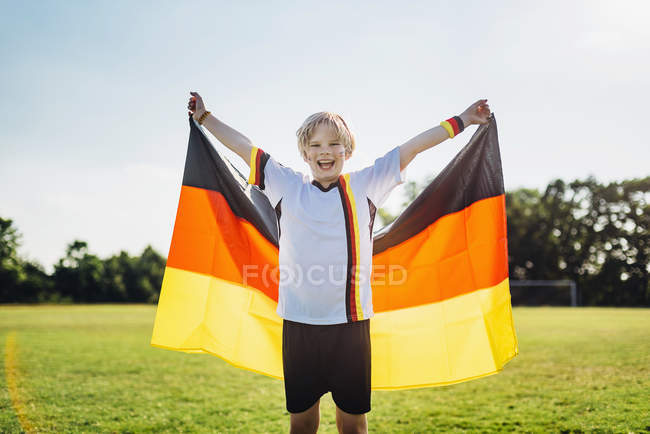 Boy, enthusiastic for soccer world championship, waving German flag — Stock Photo