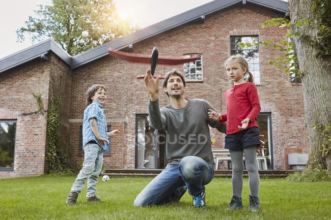 Отец с двумя детьми, играющими с игрушек самолет в саду своего дома — стоковое фото