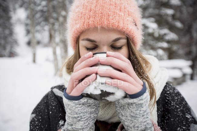 Young woman enjoying hot drink outdoors in winter — Stockfoto