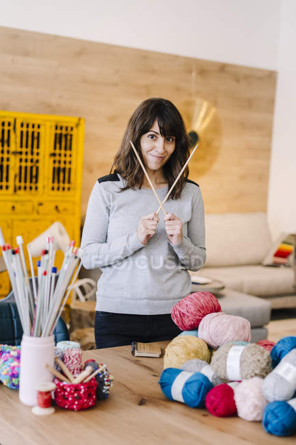 Portrait of smiling woman holding knitting needles in studio — Stock Photo