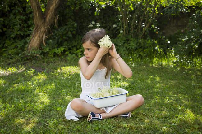 Маленька дівчинка сидить на лузі в саду з мискою вибраних квітів. — стокове фото