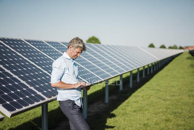 Businessman using tablet at solar park — Stock Photo