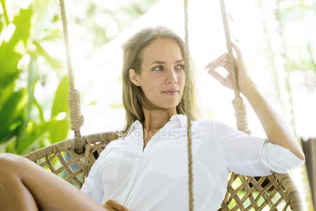 Улыбающаяся женщина расслабляется в висящем кресле — стоковое фото