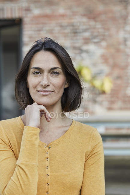 Портрет уверенной женщины перед домом — стоковое фото