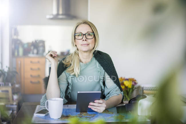 Portrait of blond businesswoman with tablet and world map — Stock Photo