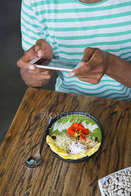 Male hands taking a picture of smoothie bowl with smartphone — Foto stock