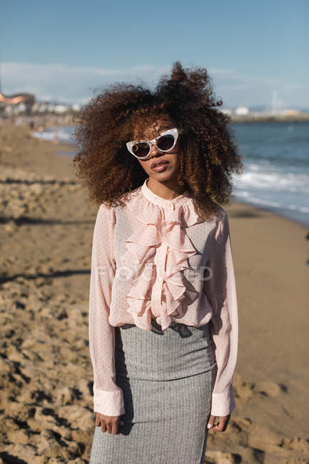 Portrait of beautiful young woman with afro hairdo standing on the beach — Stock Photo