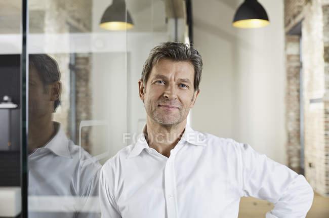 Porträt eines lächelnden Geschäftsmannes, der sich an die Glasscheibe lehnt — Stockfoto