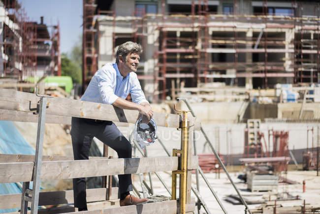 Усміхнена людина тримає міцний капелюх на будівельному майданчику, озираючись навколо — стокове фото