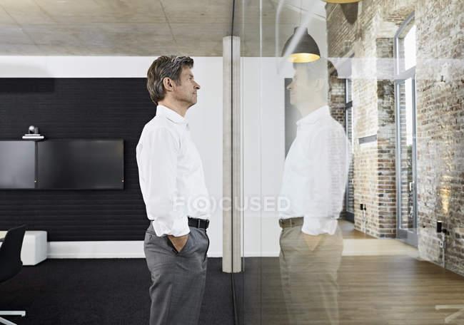 Reifer Geschäftsmann reflektiert in der Glasscheibe eines modernen Konferenzraums — Stockfoto