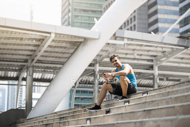 Runner wearing earphones, checking messages on his smartphone — Stock Photo