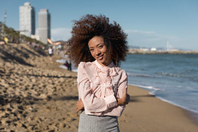Портрет посміхаючись красивою молодою жінкою з афро зачіска стоячи на пляжі — стокове фото