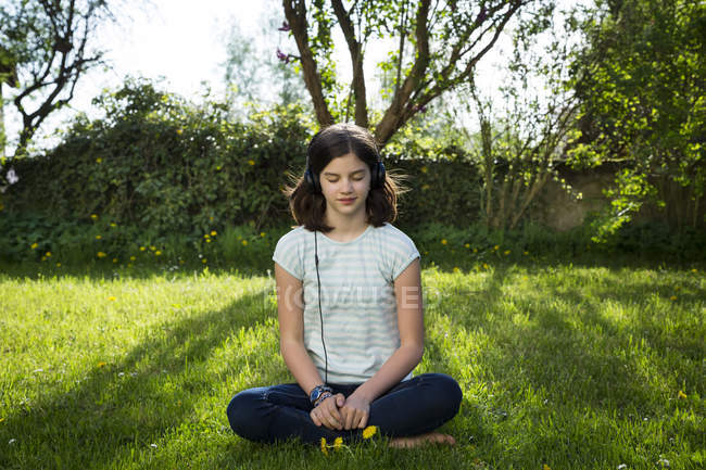 Girl sitting on meadow listening music with headphones — Stock Photo