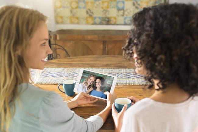 Duas mulheres olhando para sua foto em um tablet — Fotografia de Stock