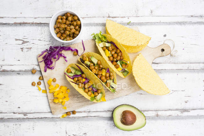 Vegetarian tacos filled with in curcuma roasted chick peas, yellow paprika, avocado, salad and red cabbage — Stock Photo