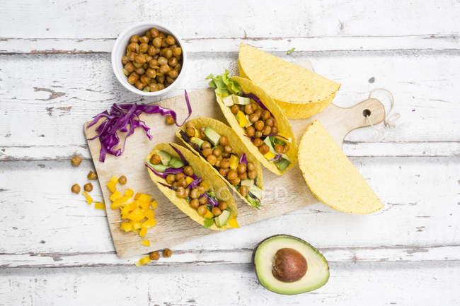 Tacos végétariens remplis de pois chiches rôtis au curcuma, paprika jaune, avocat, salade et chou rouge — Photo de stock