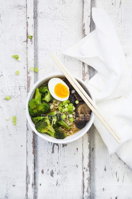 Bol de soupe Ramen avec oeuf, brocoli, nouilles, champignons shitake et oignons de printemps — Photo de stock