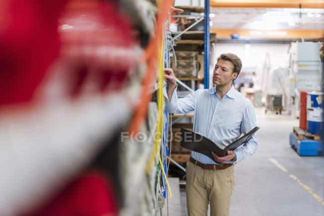 Mann in Lagerraum der Fabrik hält Ordner in der Hand, überprüft Regal — Stockfoto