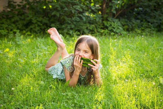 Портрет маленької дівчинки, що лежить на лузі, їсть кавун. — стокове фото