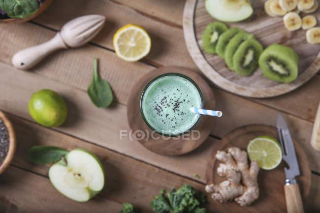 Зеленый смузи в окружении ингредиентов — стоковое фото