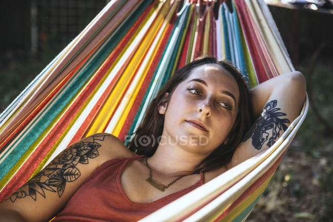 Portrait of young woman with tattoo lying in hammock — Stock Photo