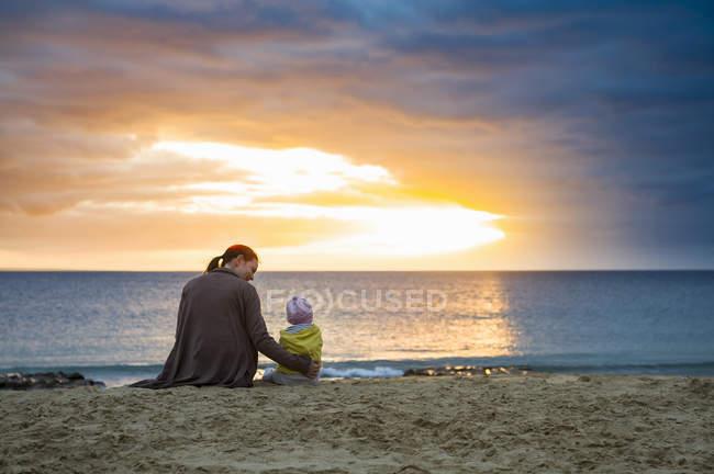 Мати з маленькою донькою сидячи на пляжі на заході сонця — стокове фото