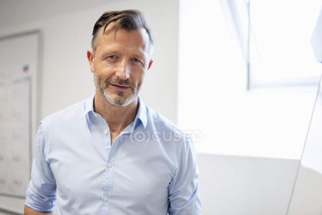 Ritratto di uomo d'affari maturo sorridente in carica — Foto stock