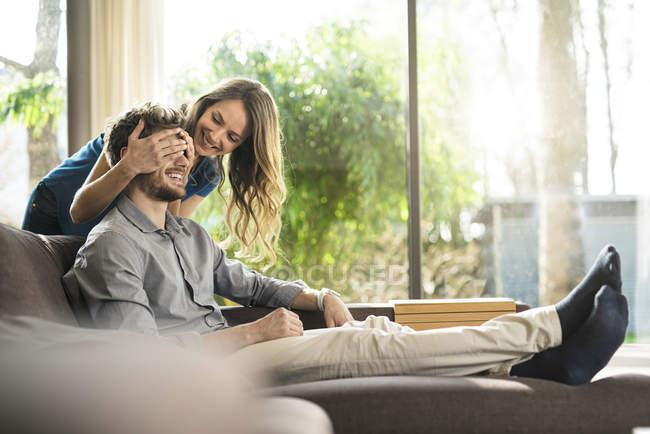 Mujer sonriente cubriendo los ojos de su novio en el sofá en casa - foto de stock