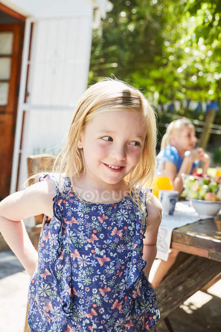 Portrait of smiling girl with mother in the background at garden table — Stock Photo