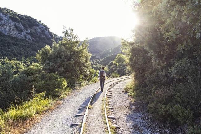 Grecia, Pilion, Milies, vista posteriore dell'uomo che cammina lungo le rotaie della ferrovia a scartamento ridotto — Foto stock