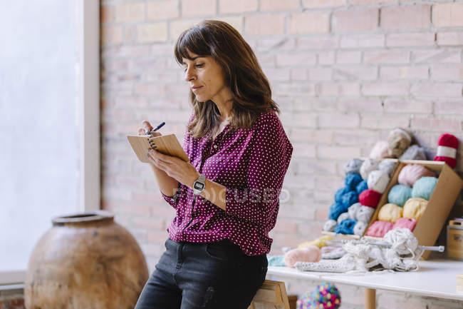 Woman in knitting studio taking notes — Stock Photo