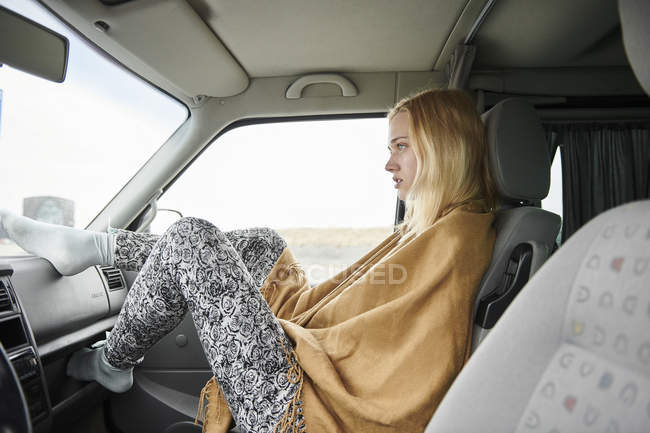 Blond young woman sitting in car looking at distance — Stock Photo