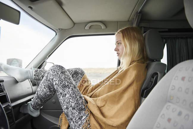 Loira jovem sentada no carro olhando para a distância — Fotografia de Stock