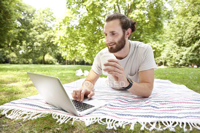 Man with coffee to go lying on blanket in a park using laptop — Stock Photo
