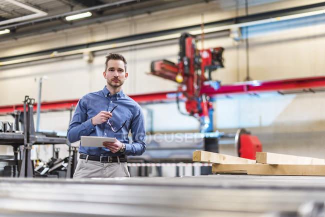 Бизнесмен держит планшет на заводе — стоковое фото