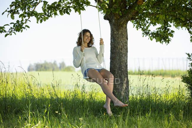Усміхаючись молода жінка, сидячи на гойдалки — стокове фото