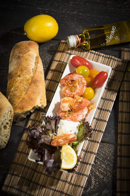 Antipasti, tuna, salad, filled paprika, white beans, black olive, shrimp, sour cream, tomato and white bread — Stock Photo