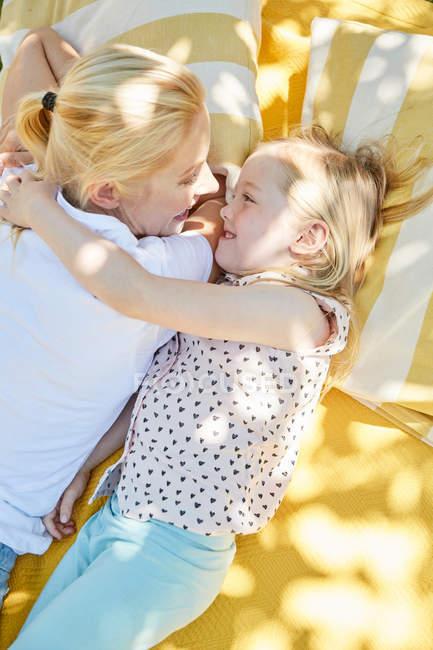 Chica feliz con la madre acostada en la manta - foto de stock