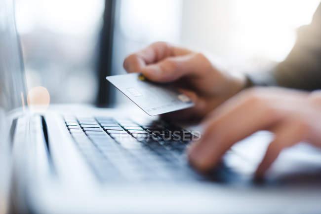 Homme à l'aide d'ordinateur portable et carte de crédit du portefeuille, close-up — Photo de stock