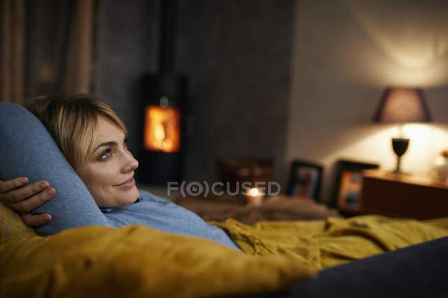 Sorrindo mulher relaxante no sofá em casa à noite — Fotografia de Stock
