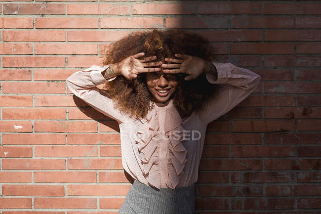 Portrait of smiling beautiful young woman with afro hairdoat brick wall in sunshine — Stock Photo