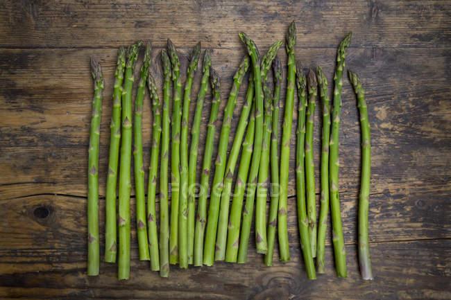 Lanças verdes orgânicas dos espargos na madeira — Fotografia de Stock