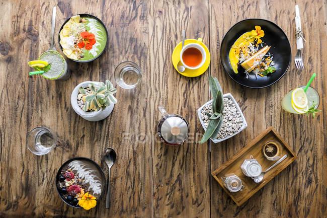 Разнообразие экзотических украшенных блюд на деревянной сказке — стоковое фото