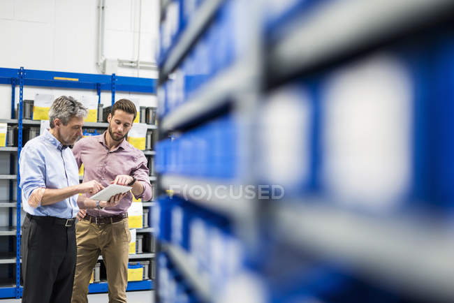 Businessmen using tablet during meeting in storage — Stock Photo