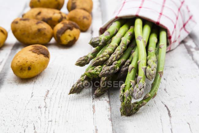 Зеленая спаржа и картофель на белом дереве — стоковое фото