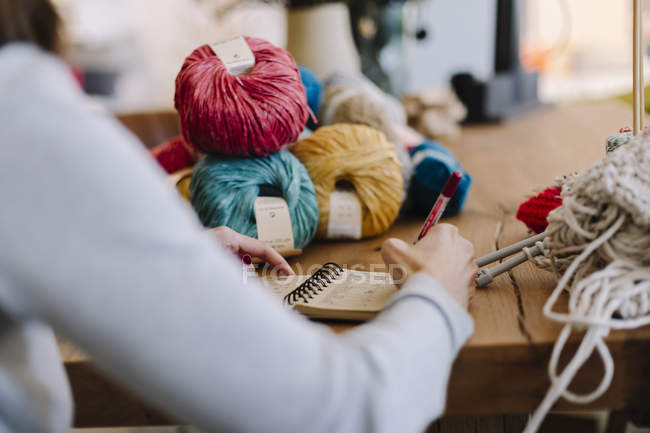 Close-up of woman taking notes on table with knitting — Stock Photo