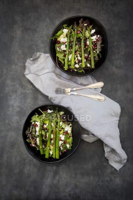 Смешанный салат с жареной зеленой спаржей, фетой и семенами граната — стоковое фото