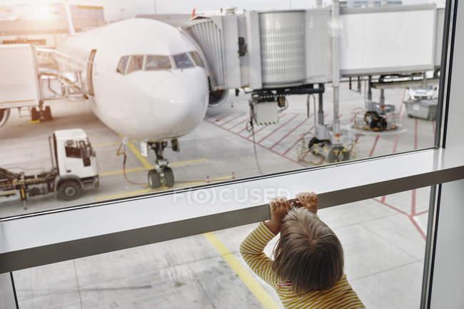 Menina olhando através de janela para avião no avental — Fotografia de Stock