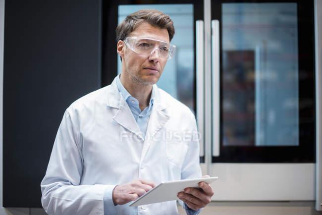 Retrato del hombre con bata de laboratorio y gafas de seguridad sosteniendo la tableta en la máquina - foto de stock